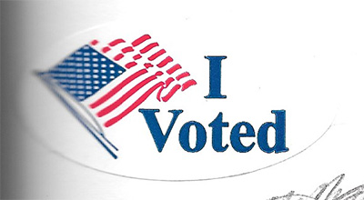 "A sticker with an American flag that reads ""I voted""."